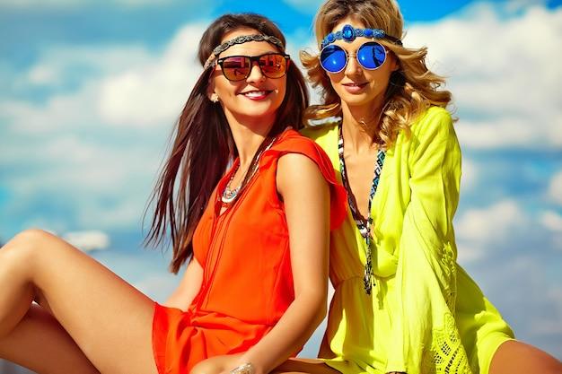 Modeporträt der jungen hippie-frauenmodelle im sonnigen sommertag in den hellen bunten hipster-kleidern
