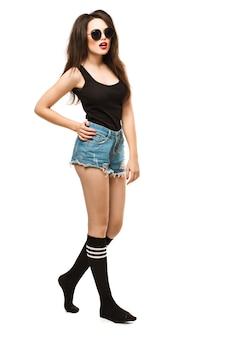 Modeporträt der jungen hübschen hipsterfrau mit großen vollen hellen lippen, die stilvolles schwarzes outfit, denim-beute-shorts um große sonnenbrillenmode lange sockenfüße und schwarzes t-shirt tragen. wandhintergrund