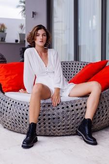 Modeporträt der jungen hübschen stilvollen frau im weißen hellen sommerkleid und in den großen schwarzen massiven stiefeln an der luxuriösen reichen villa
