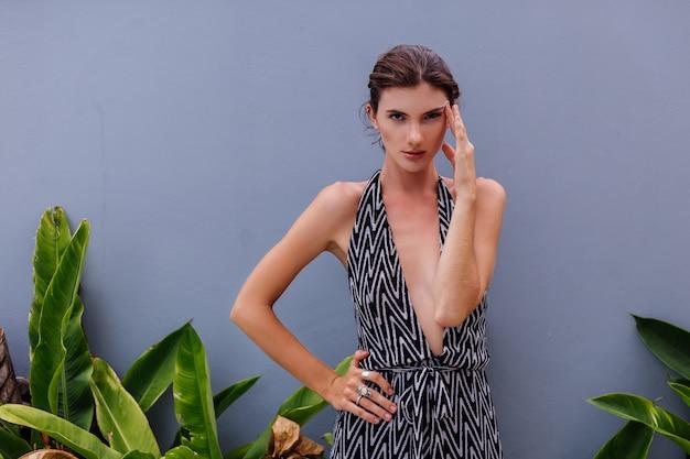 Modeporträt der jungen kaukasischen stilvollen modellfrau im klassischen langen overall, der an der wand und an den tropischen blättern naturlicht im freien aufwirft