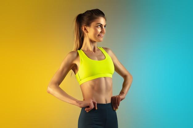 Modeporträt der jungen passform und der sportlichen frau auf gradientenhintergrund. perfekter körper bereit für den sommer.