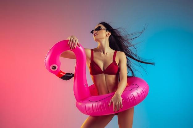 Modeporträt der jungen passform und der sportlichen kaukasischen frau in der stilvollen roten badebekleidung auf gradient