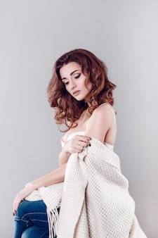 Modeporträt der jungen schönen sexy frau mit dem langen gewellten haar. hübsches mädchen, das im weißen bh oder in den dessous im studio sitzt. modestil getönten farben porträt