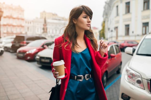Modeporträt der jungen schönen stilvollen frau, die in der stadtstraße im roten mantel, herbstarttrend geht, kaffee trinkend, lächelnd, glücklich, blaues seidenkleid tragend