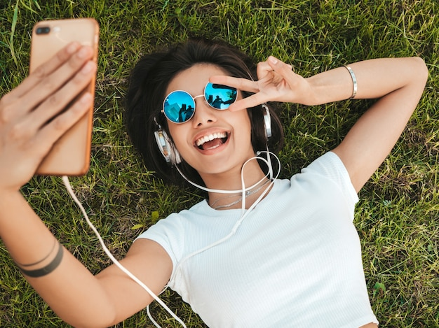 Modeporträt der jungen stilvollen hipsterfrau, die auf dem gras im park liegt. mädchen trägt trendiges outfit. lächelndes modell, das selfie macht. frau, die musik über kopfhörer hört. draufsicht
