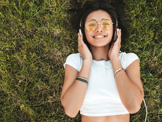 Modeporträt der jungen stilvollen hipsterfrau, die auf dem gras im park liegt. mädchen trägt trendiges outfit. lächelndes modell genießen ihre wochenenden. frau, die musik über kopfhörer hört. draufsicht