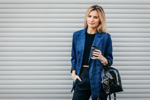 Modeporträt der jungen stilvollen hipsterfrau, die auf der straße geht, niedliches trendiges outfit trägt und leckeren kaffee trinkt