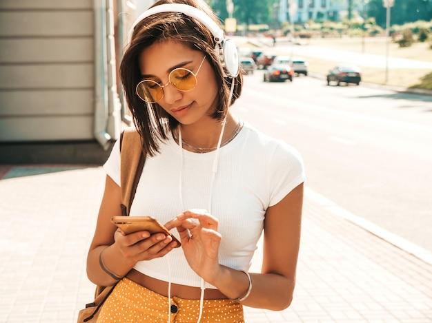 Modeporträt der jungen stilvollen hipsterfrau, die in der straße geht. mädchen, das niedliches trendiges outfit trägt. lächelndes modell genießen ihre wochenenden, reisen mit rucksack. frau, die musik über kopfhörer hört