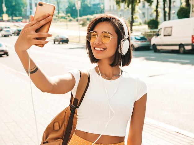 Modeporträt der jungen stilvollen hipsterfrau, die in der straße geht. mädchen, das selfie macht. lächelndes modell genießen ihre wochenenden mit rucksack. frau, die musik über kopfhörer hört