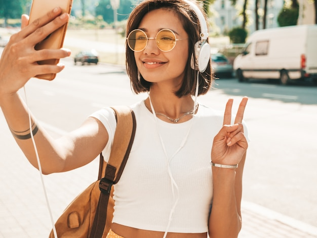 Modeporträt der jungen stilvollen hipsterfrau, die in der straße geht. mädchen, das selfie macht und friedenszeichen zeigt. lächelndes modell genießen ihre wochenenden mit rucksack. frau, die musik über kopfhörer hört