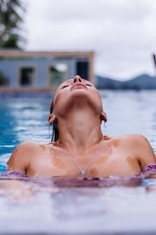 Modeporträt der kaukasischen frau im bikini im blauen schwimmbad im urlaub am tageslicht des tages