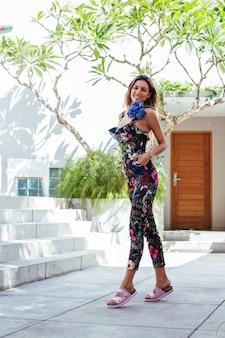 Modeporträt der kaukasischen frau im stilvollen sommeroverall mit blumen außerhalb der villa