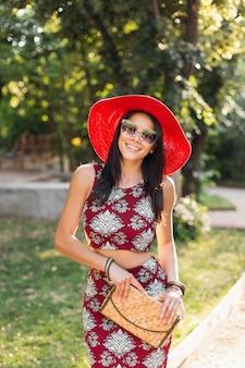 Modeporträt der lächelnden attraktiven stilvollen frau, die im park im sommer-outfit bedrucktes kleid geht und trendige accessoires, geldbörse, sonnenbrille, roten hut trägt, im urlaub entspannend