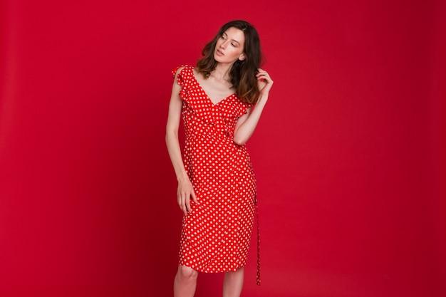 Modeporträt der lächelnden jungen frau im rot gepunkteten kleid auf rot