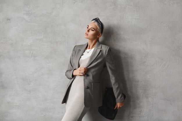 Modeporträt der modischen jungen frau im trendigen outfit, das drinnen aufwirft
