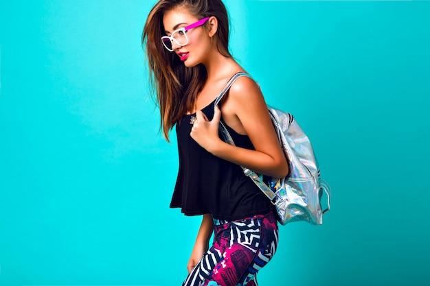Modeporträt der schönen frau, gebräuntes perfektes skifahren, helles make-up, trendiges sportliches outfit, bedruckte leggings, silberner rucksack