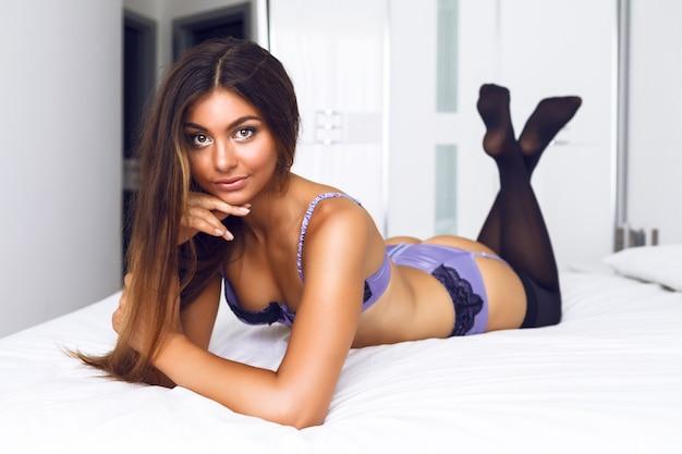 Modeporträt der schönen sinnlichen frau mit perfektem körper und sexy seidenwäsche, genießen sie ihren morgen und entspannen sie sich im großen weißen schlafzimmer.