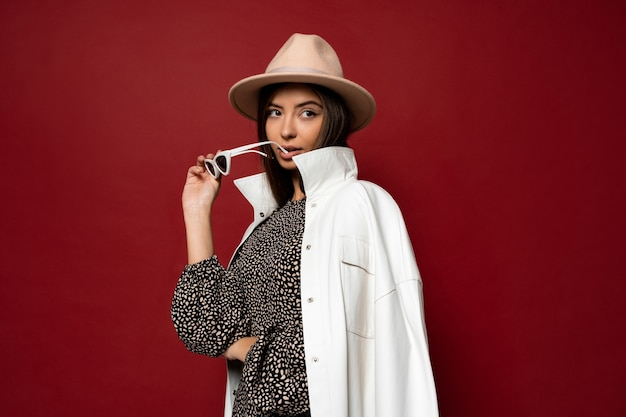 Modeporträt der schönen stilvollen mageren brünetten frau mit gekleidetem weißen mantel und beigem hut, der sonnenbrille hält. trendiger modestil für herbst oder winter.