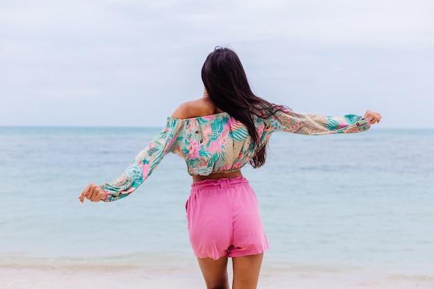 Modeporträt der stilvollen frau im bunten druck-langarmoberteil und in den rosa shorts am strand, tropischer hintergrund.
