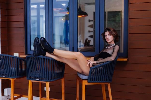 Modeporträt der stilvollen kaukasischen villa im ganzkörperanzug und in den schwarzen stiefeln außerhalb der villa