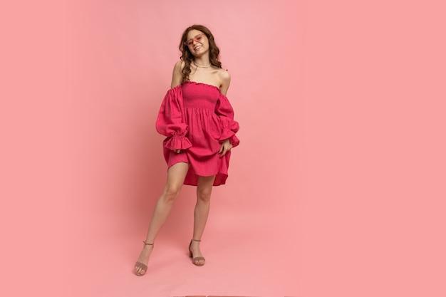 Modeporträt der stilvollen rothaarigen frau, die auf rosa pfandrechtkleid mit ärmeln auf rosa aufwirft
