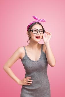 Modeporträt des asiatischen mädchens mit der sonnenbrille, die auf rosa hintergrund steht.