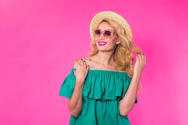 Modeporträt des glamourmädchens, der niedlichen emotionen, der stilvollen hipster kleidet sonnenbrille auf rosa wand mit copyspace.