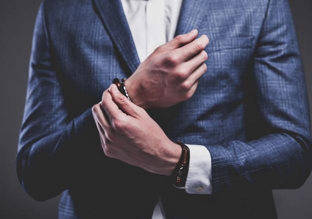 Modeporträt des hübschen modellmanns des jungen geschäftsmannes, gekleidet im eleganten blauen anzug auf grau.