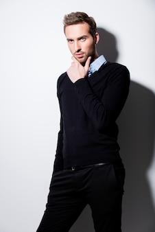 Modeporträt des jungen mannes im schwarzen pullover und im blauen hemd mit kontrastschatten.