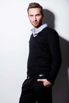 Modeporträt des jungen mannes im schwarzen pullover und im blauen hemd mit kontrastschatten