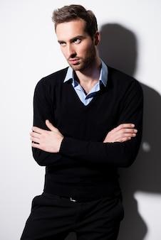 Modeporträt des jungen mannes im schwarzen pullover und im blauen hemd mit verschränkten armen