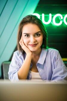 Modeporträt des jungen modells, das am café auf der terrasse am sonnigen tag arbeitet