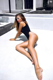 Modeporträt des modells mit atemberaubendem gebräuntem körper, kreativem kunst-make-up, auf dem boden liegend, stilvollen minimalistischen schwarzen bikini tragend.