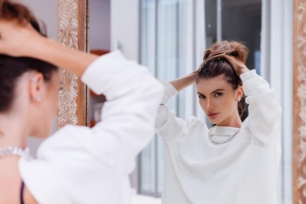Modeporträt des professionellen modells der jungen kaukasischen frau im weißen blazer und im silbernen kettenblick im spiegel bei luxusvilla