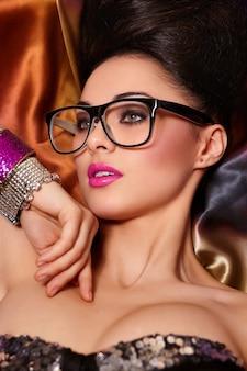 Modeporträt des schönen brünetten mädchenmodells in den gläsern mit birght make-up rosa lippen und ungewöhnlicher frisur hell bunt mit zubehör