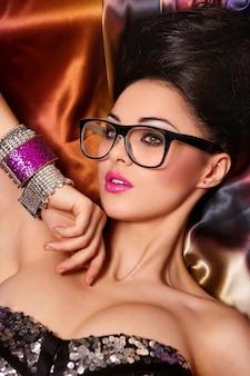 Modeporträt des schönen brünetten mädchenmodells in den gläsern mit hellen make-up-rosa lippen und ungewöhnlicher frisur hell bunt