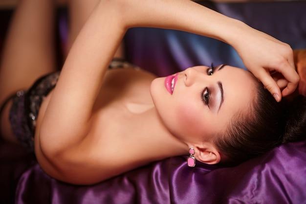 Modeporträt des schönen brünetten mädchenmodells mit hellen make-up rosa lippen und frisur hell bunt auf dem bett liegend