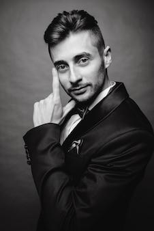 Modeporträt des schönen eleganten mannes mit dem gelockten haar, das smoking trägt, das auf grauem hintergrund im studio aufwirft. schwarzweiss-foto