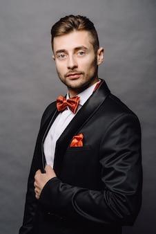 Modeporträt des schönen eleganten mannes mit dem lockigen haar, das smoking trägt, das auf grauem hintergrund im studio aufwirft
