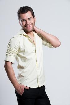 Modeporträt des schönen glücklichen mannes im gelben hemd mit hand nahe gesicht stellt
