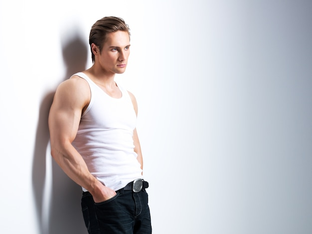 Modeporträt des schönen jungen mannes im weißen hemd, das seitlich schaut, wirft über wand mit kontrastschatten auf.
