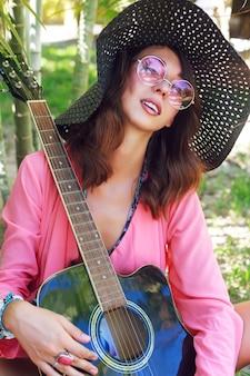 Modeporträt des schönen mädchens mit natürlichem make-up und flauschigen brünetten haaren, die am garten mit gitarre aufwerfen. trägt hut und runde trendige rosa sonnenbrille.
