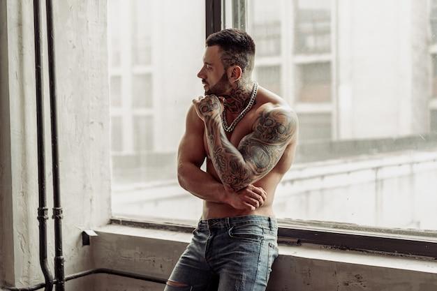Modeporträt des sexy nackten männlichen modells mit tätowierung und einem schwarzen bart, der in der heißen pose nahe am fenster steht. loft zimmer interieur mit grauer betonwand.