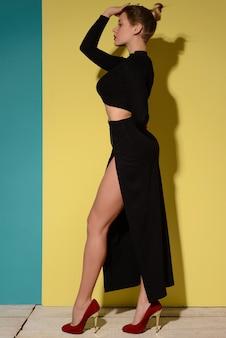 Modeporträt des stilvollen gebräunten mädchens im schwarzen kleid ohne ärmel mit langem schnitt