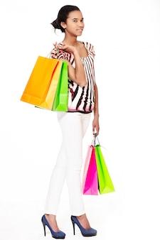 Modeporträt des stilvollen lächelnden lässigen jungen weiblichen schönen schwarzen amerikanischen mädchens, das einkaufstaschen gegen weißen hintergrund trägt