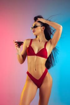 Modeporträt einer jungen, fitten und sportlichen frau mit cocktail in stilvoller roter luxusbadebekleidung an einer wand mit farbverlauf, perfekter körper für den sommer bereit summer