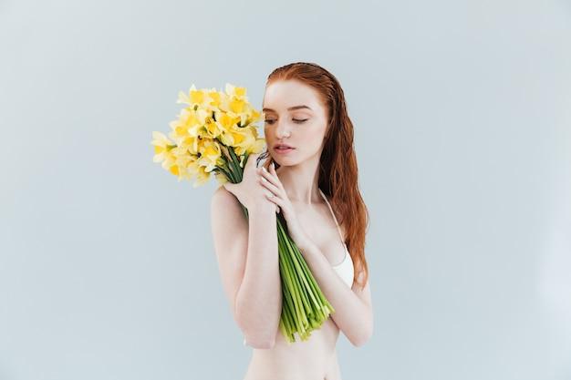 Modeporträt einer jungen rothaarigen frau, die narcisuss blumen hält