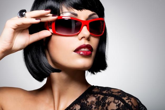 Modeporträt einer schönen brünetten frau mit schussfrisur mit roter sonnenbrille