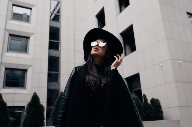 Modeporträt eines eleganten jungen models in schwarzem mantel, stilvollem hut und brille, das in der nähe des einkaufszentrums posiert