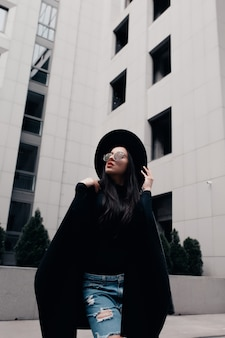 Modeporträt eines hübschen jungen models in schwarzem mantel, stilvollem hut und brille, das in der nähe des einkaufszentrums posiert